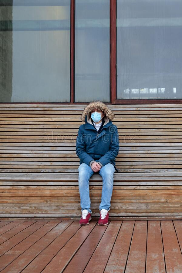 Sick man with a hood sitting alone on bench, wearing protective facial mask. coronavirus pandemic. Sick man with a hood sitting alone on bench, wearing royalty free stock photo