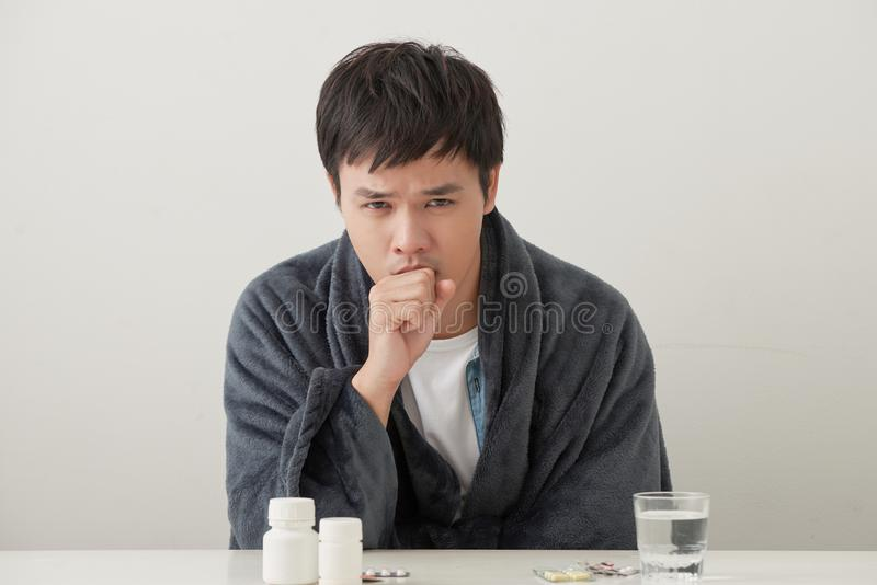 Sick man lying on bed and coughing a lot.  royalty free stock image