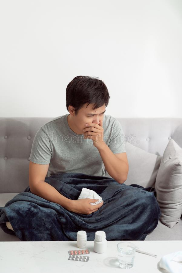 Sick man lying on bed and coughing a lot.  stock photography
