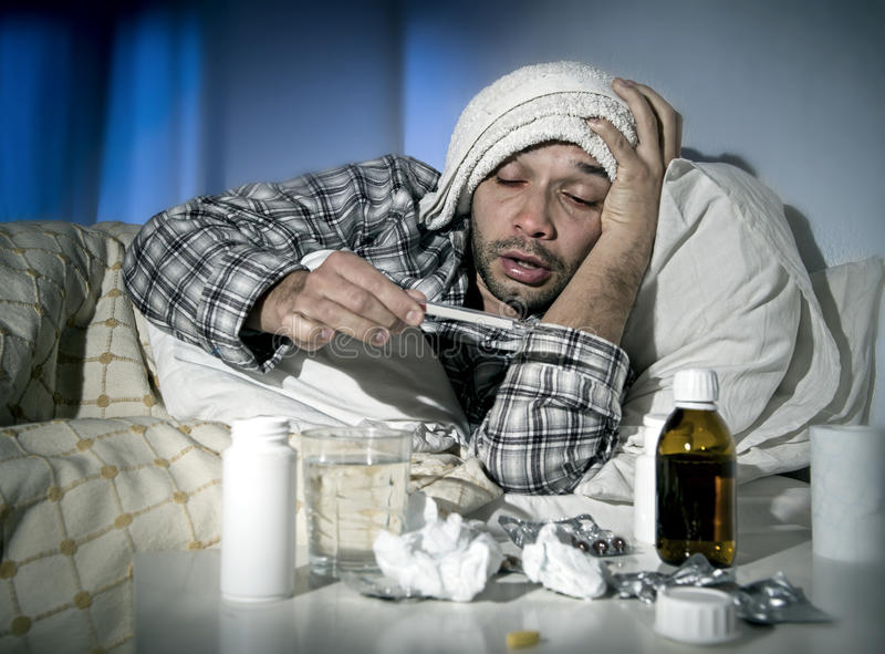 Sick man lying in bed suffering cold and winter flu virus having medicine and tablets stock images