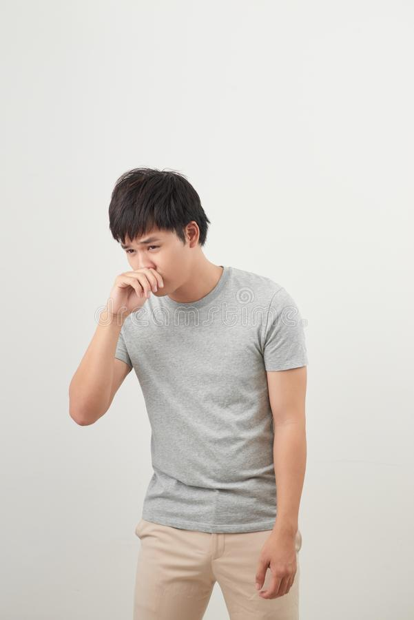 Sick man with runny nose portrait; sick asian man with runny nose, cold, flu, illness, contagious disease, health care concept; royalty free stock photo