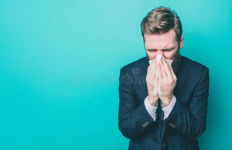 Sick man is standing and sneezing. He caught some cold. Man is suffering and standing on the side. Isolated on blue stock photos