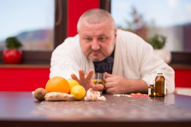 Sick man suffering cold and winter flu virus drinking tea.  royalty free stock image