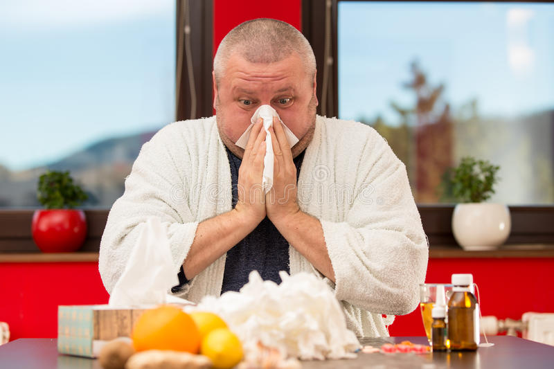 Sick man suffering cold and winter flu virus drinking tea.  royalty free stock images