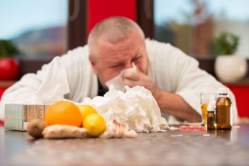 Sick man suffering cold and winter flu virus drinking tea.  royalty free stock photos