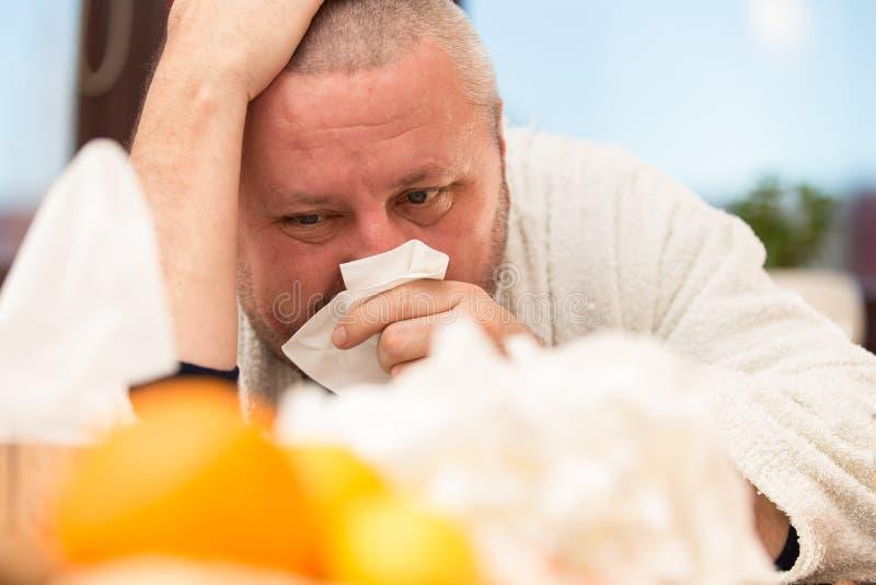 Sick man suffering cold and winter flu virus drinking tea.  stock photos
