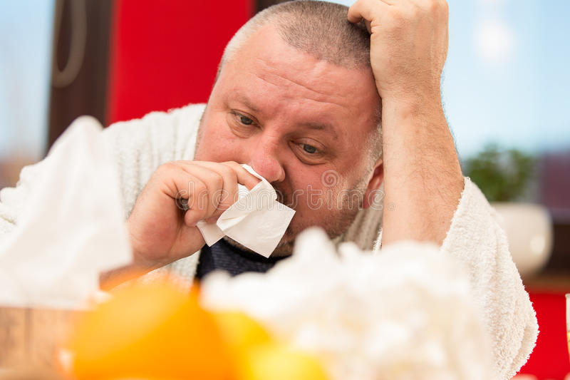 Sick man suffering cold and winter flu virus drinking tea.  stock photography