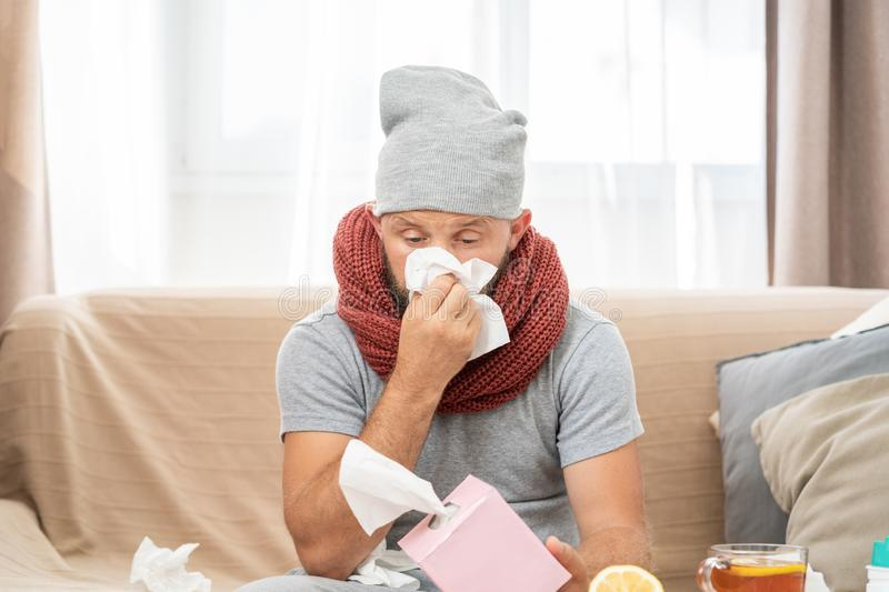 Sick man wearing grey hat and scarf, blowing nose and sneeze into tissue. stock photo