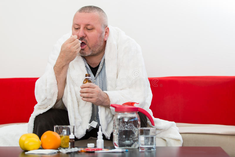 Sick man wearing pajama suffering cold and winter flu virus having medicine stock photos