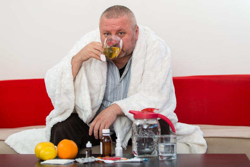 Sick man wearing pajama suffering cold and winter flu virus having medicine stock photo