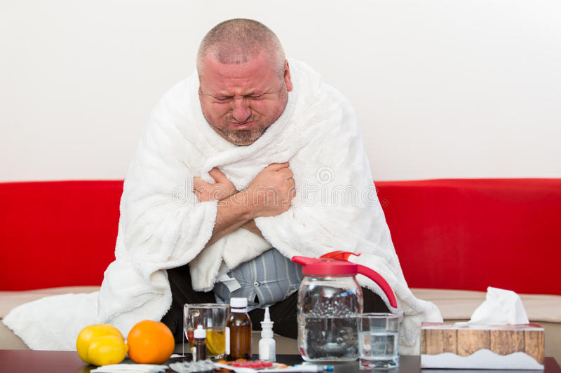 Sick man wearing pajama suffering cold and winter flu virus having medicine royalty free stock images