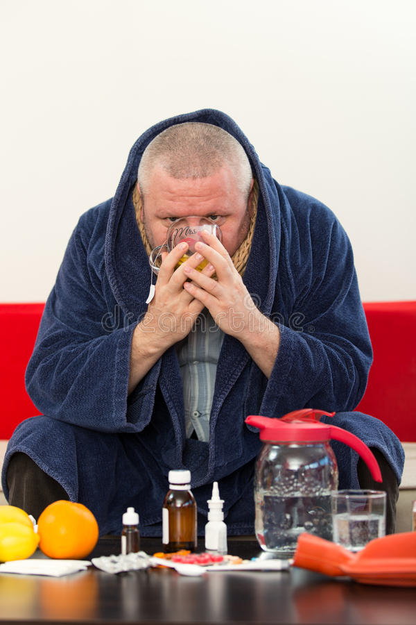 Sick man wearing pajama suffering cold and winter flu virus having medicine royalty free stock photography