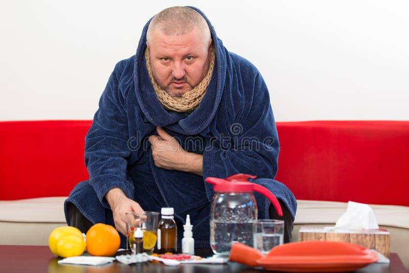 Sick man wearing pajama suffering cold and winter flu virus having medicine.  stock image
