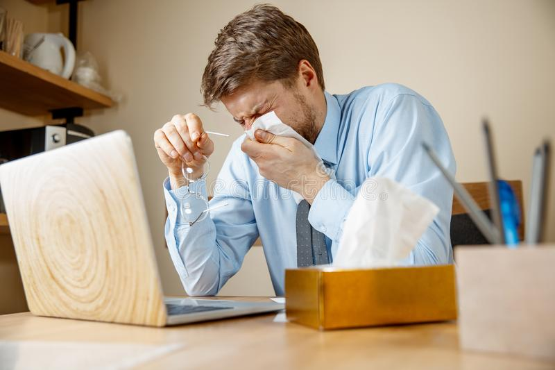 Sick man while working in office, businessman caught cold, seasonal flu. Sick man with handkerchief sneezing blowing nose while working in office, businessman royalty free stock photos
