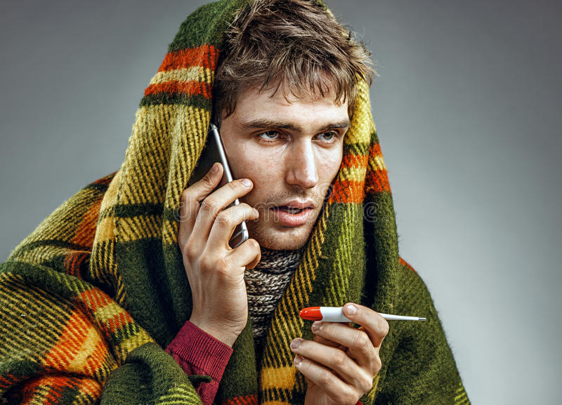 Sick man wrapped in blanket with a high temperature calling on the phone royalty free stock photo