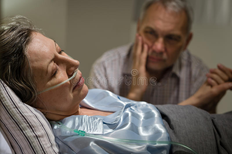 Sick mature woman lying in bed royalty free stock photos