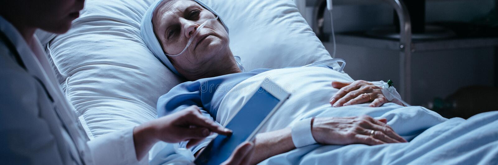 Sick, middle-aged woman looking sadly at her doctor who is check stock photos