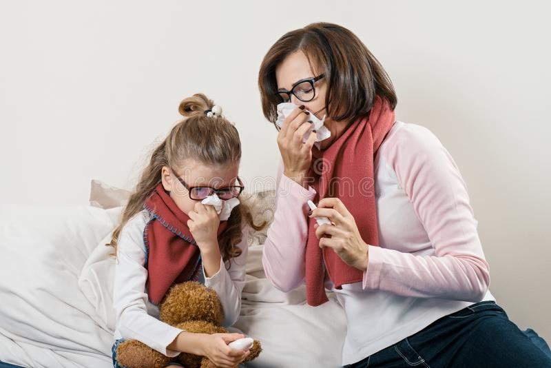 Sick mother and child sneezing in handkerchief, holding nasal spray, cold season stock photography