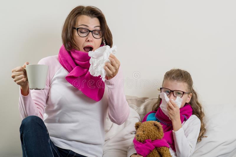 Sick mother and daughter. A woman with a runny nose, she sneezes, using a handkerchief, drinking hot tea, medicine. Sick mother and daughter. women with a runny stock image