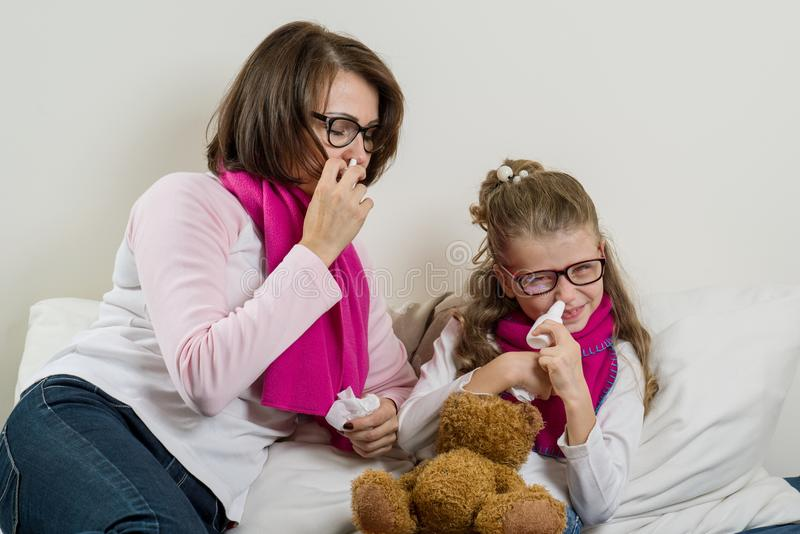 Sick mother and daughter. A woman and a child with a runny nose, they sneeze, use a handkerchief. Sick mother and daughter. A women and a child with a runny royalty free stock image