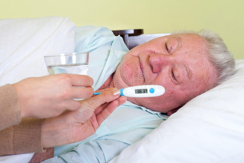 Sick old man having fever. Picture of a sick old man in bed having fever stock images