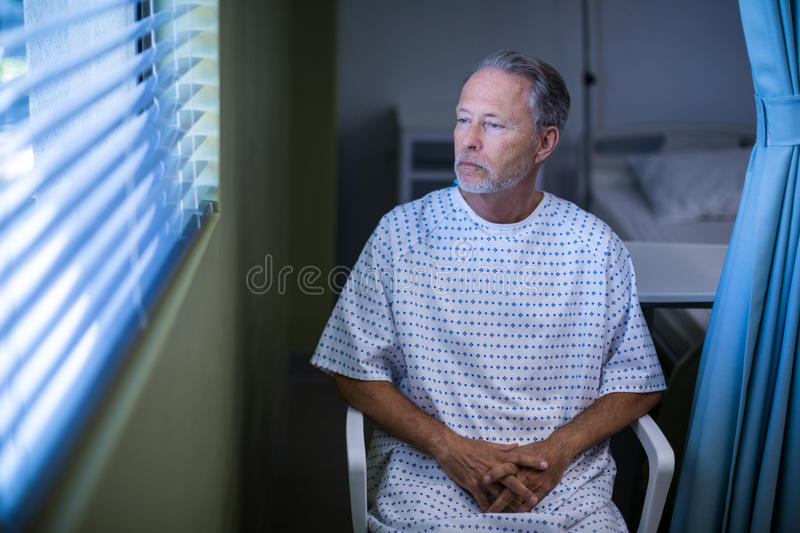 Sick patient sitting on chair and looking through window blinds stock photo