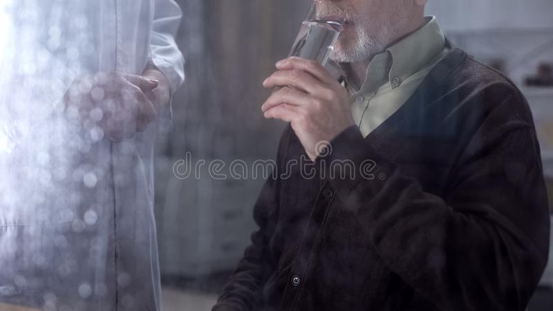 Sick retired gentleman drinking water glass, nurse looking after patient, care. Stock photo stock photography