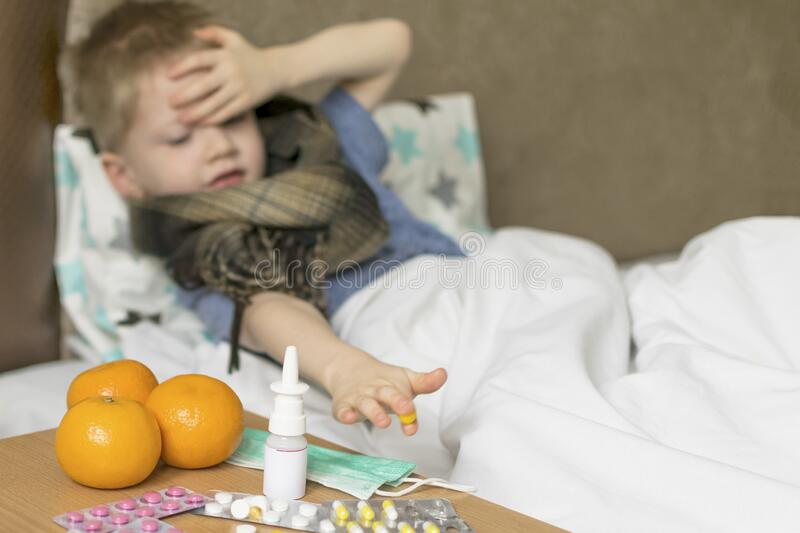 A sick sad child with a temperature and a headache lies in bed next to medication. Flu colds disease virus. Bacterium stock photography
