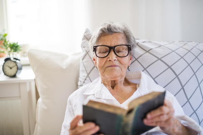 Sick senior woman with glasses reading bible in bed at home or in hospital. A sick senior woman with glasses lying in bed at home or in hospital, reading bible royalty free stock images