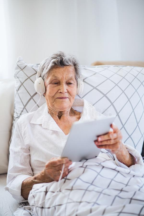Sick senior woman with headphones and tablet lying in bed at home or in hospital. A sick senior woman with headphones and tablet lying in bed at home or in stock image