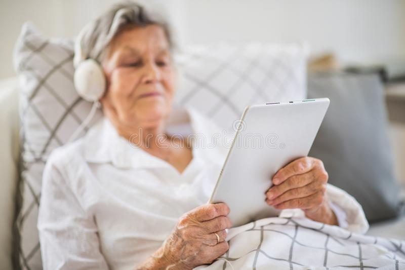 Sick senior woman with headphones and tablet lying in bed at home or in hospital. A sick senior woman with headphones and tablet lying in bed at home or in royalty free stock images