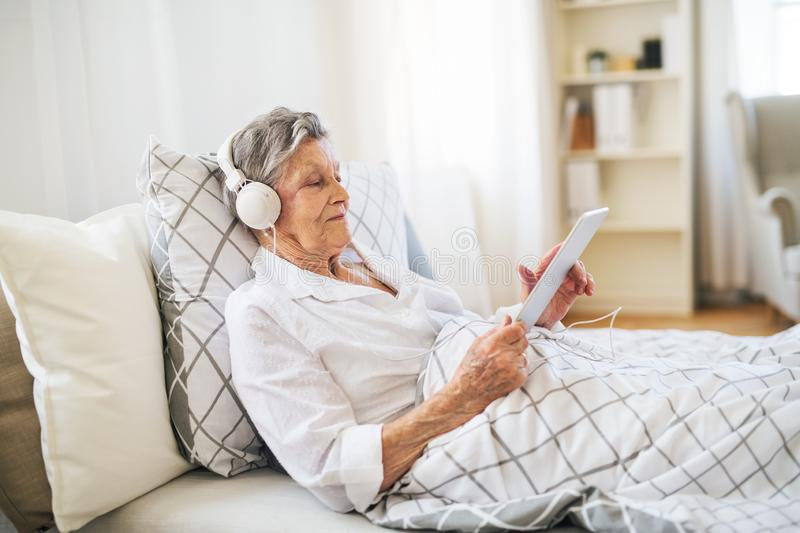 Sick senior woman with headphones and tablet lying in bed at home or in hospital. A sick senior woman with headphones and tablet lying in bed at home or in stock images