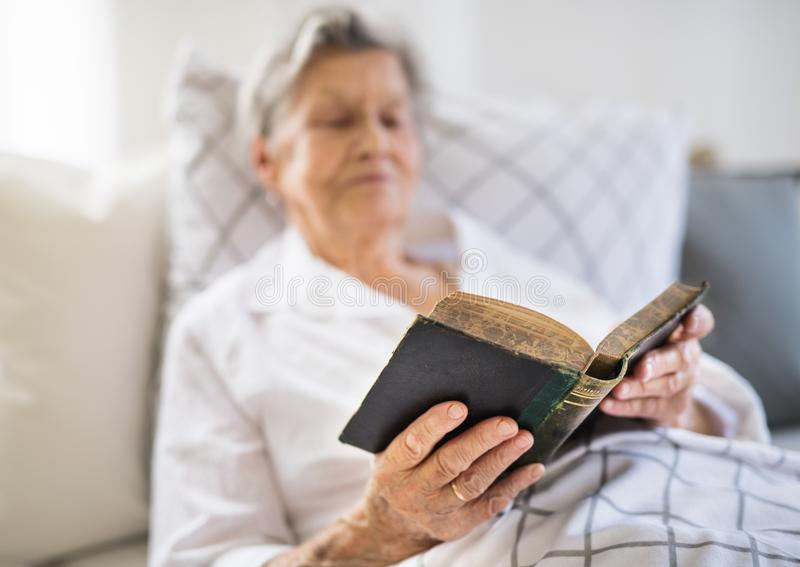 Sick senior woman reading bible book in bed at home or in hospital. A sick senior woman lying in bed at home or in hospital, reading bible book stock photos