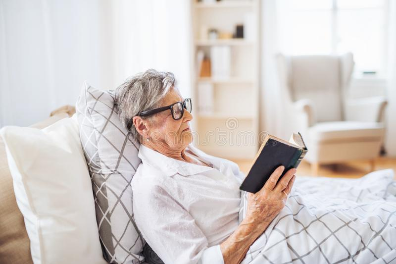 Sick senior woman reading bible book in bed at home or in hospital. A sick senior woman with eyeglasses lying in bed at home or in hospital, reading bible book royalty free stock images
