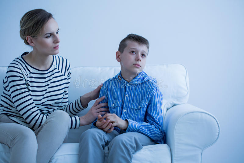 Sick son sitting on sofa stock images