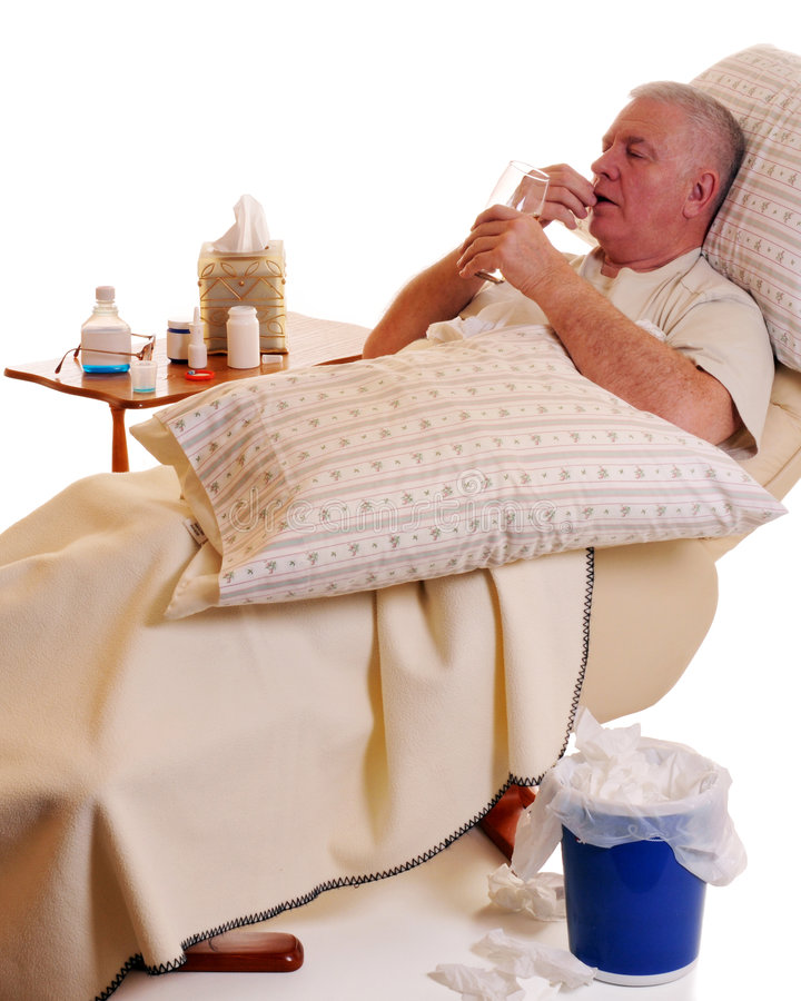 Sick and Taking Meds. Senior man in a recliner, sick and taking medication for his illness stock photography