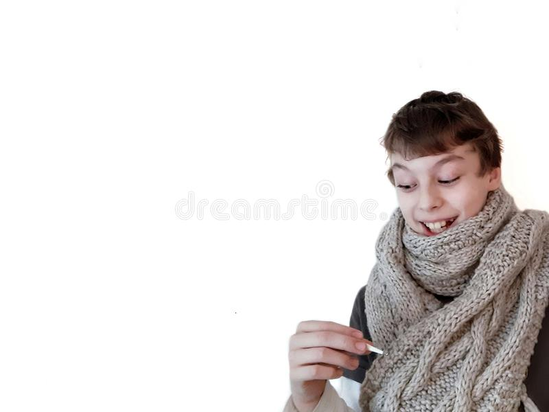 Sick teen in grey knitted scarf with thermometer on white background royalty free stock images