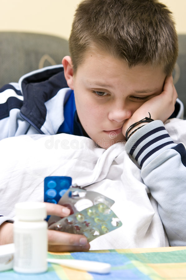 Sick teenage boy and medicines stock photo