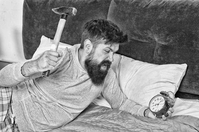 Sick and tired. Irritated guy destroy annoying clock. Man awake unhappy with alarm clock ringing. Sleep longer. Healthy stock photos