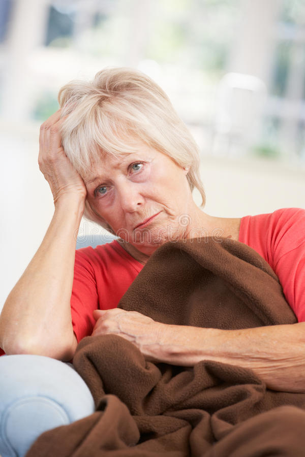 Sick, unhappy older woman at home stock image