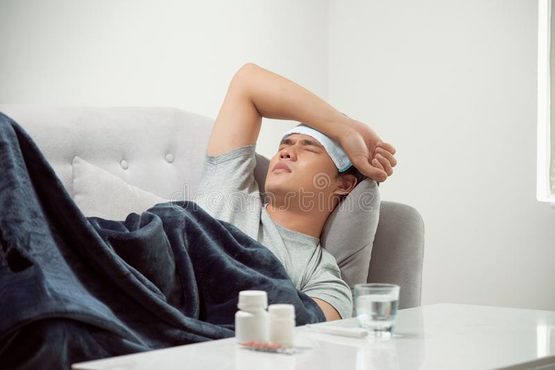 Sick wasted man lying in sofa suffering cold and winter flu virus having medicine tablets in health care concept looking. Temperature on thermometer royalty free stock image