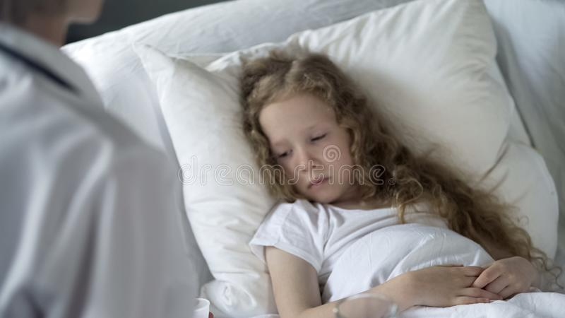 Sick weak girl lying in bed in hospital, doctor examining patient, healthcare royalty free stock photo
