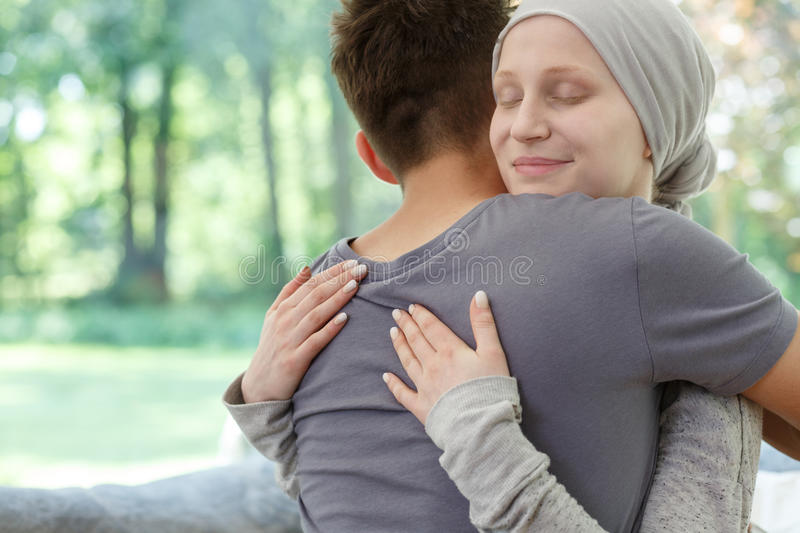 Sick wife hugging husband. After successful therapy against brain cancer royalty free stock photos