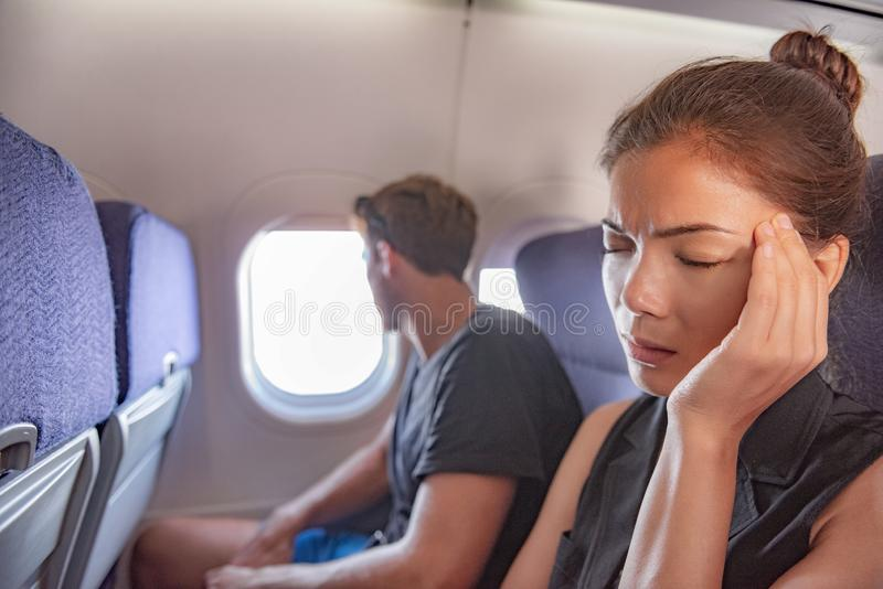 Sick woman in airplane fear of flying inside plane cabin with headache. Asian passenger on travel feeling sick with stress anxiety stock photos