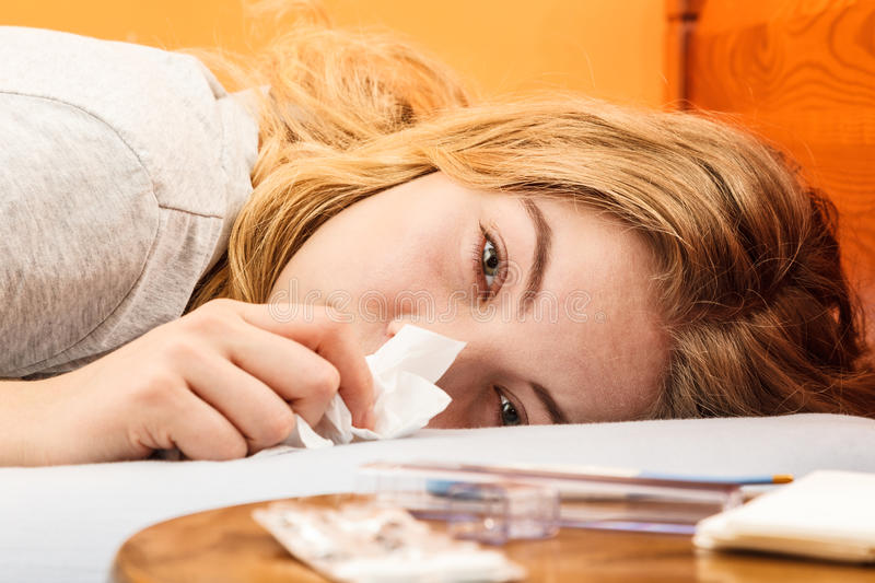 Sick woman in bed sneezing in tissue. Cold. stock image