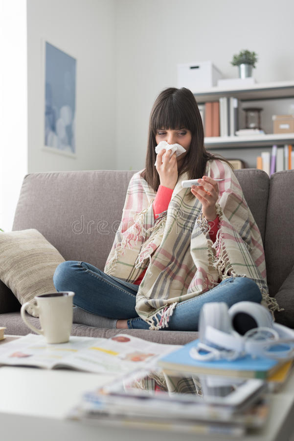 Sick woman with cold and flu. She is resting on the sofa at home and measuring body temperature with a thermometer royalty free stock photography