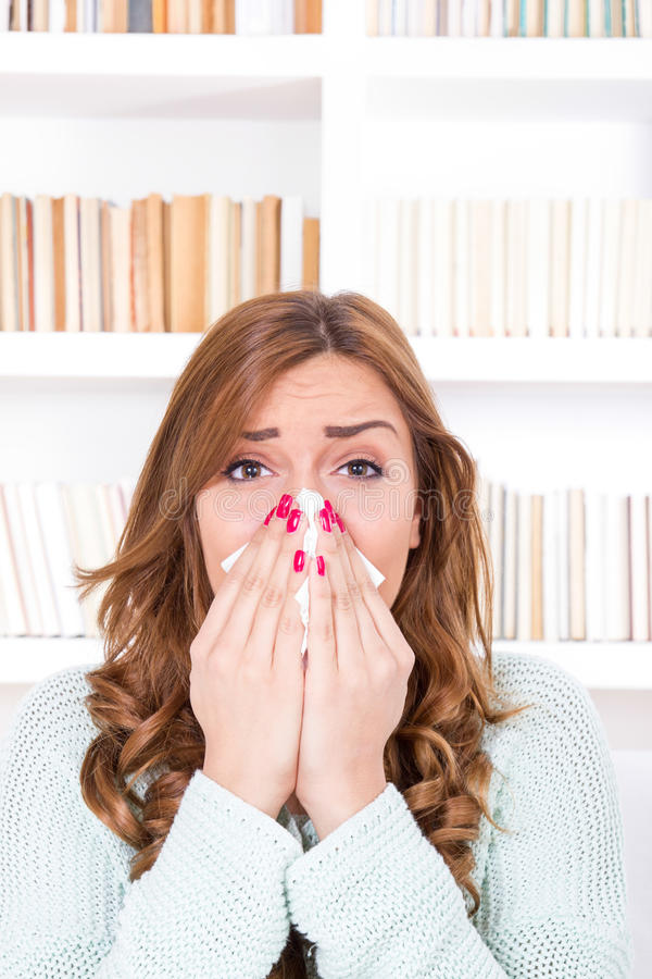Sick woman with cold and virus sneezing into tissue. Beautiful sick woman with cold and virus sneezing into tissue stock images