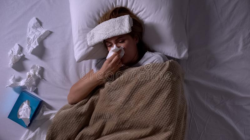 Sick woman with compress and napkins lying in bed, sneezing, seasonal allergy royalty free stock photos