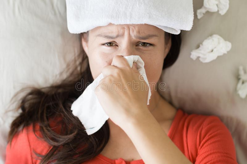 Sick woman coughing and blowing her nose, lying in bed stock photo