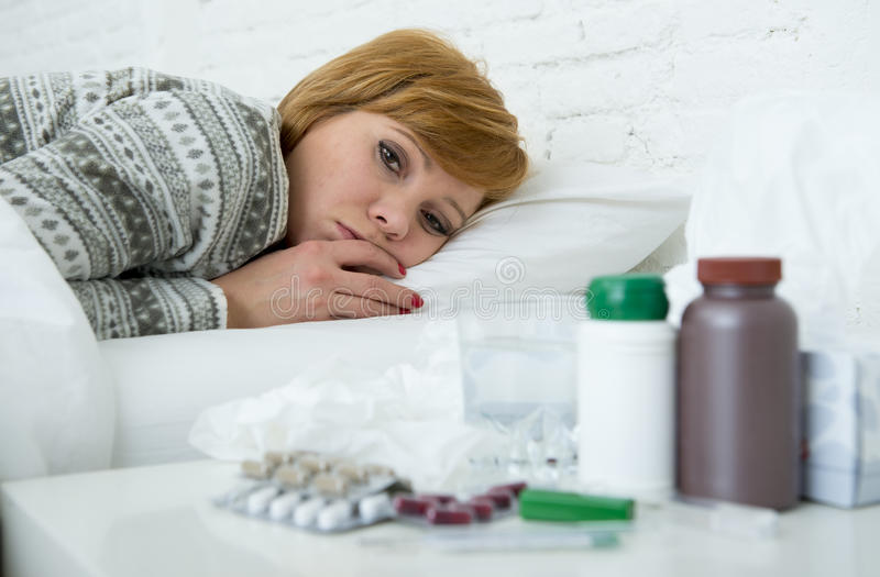 Sick woman feeling bad ill lying on bed suffering headache winter cold and flu virus having medicines. Young sick woman feeling ill and bad lying on bed royalty free stock photos